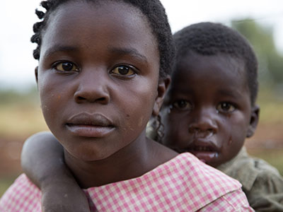 A young girl looks intently at the camera while holding a crying young boy on her back.