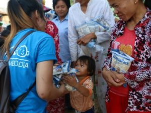 A girl from Kinship Cambodia distributing food packets