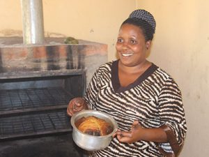 A women from Uganda baking a cake
