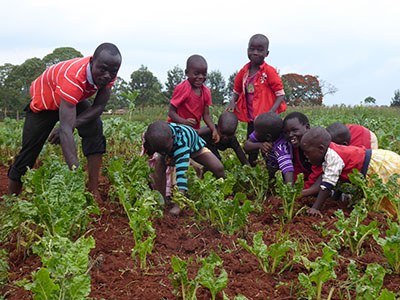 Henry Rajab teaches other Kinship Kids about farming.