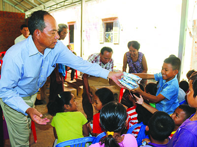 A Kinship Leader in Cambodia hands packets of food to a smiling child.