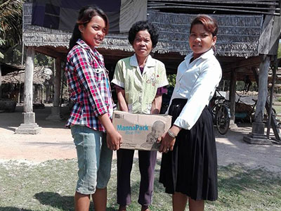 Chhan Soknet holding a box of life-saving food, supplied by Feed My Starving Children, with her family.