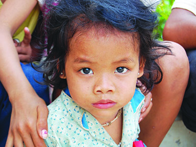 A serious young girl from Cambodia looks straight into the camera.