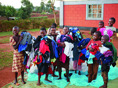 A group of young kids excitedly hold bundles of new clothes in their hands