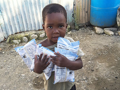 A young boy from the Dominican Republic stands holding Manna Pack food packets generously donated by Feed My Starving Children.