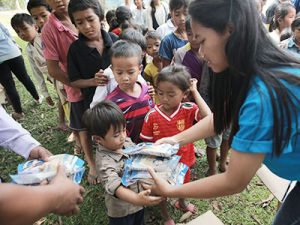 Young woman in Cambodia hands Manna Pack food packets from Feed My Starving Children to a young boy