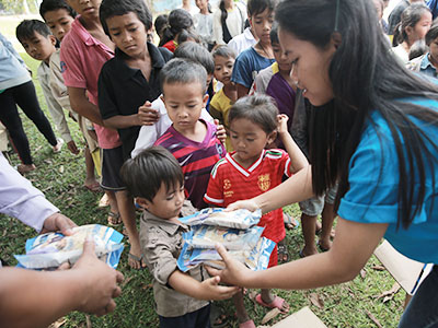 In Cambodia, a young woman hands Manna Pack food packets from Feed My Starving Children to a young child.
