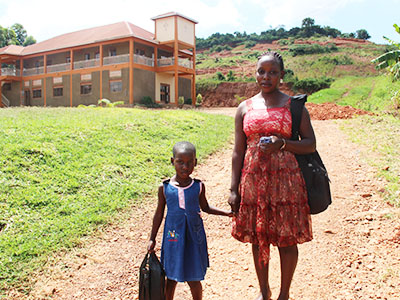 A young girl in a blue dress stands next to her mom, holding her hand, at the Kireka Kinship Project in Uganda.
