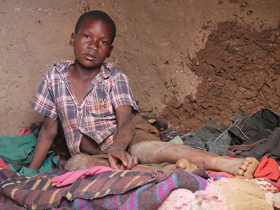 Young boy with dirty clothes sits solemnly on blankets in a mud house.