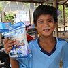 Young boy in Cambodia holds up food packet and smiles