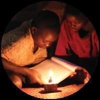 Children reading by kerosene lamp