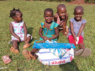Smiling children in Uganda receiving supplies