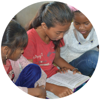 Girls in Cambodia reading a Bible