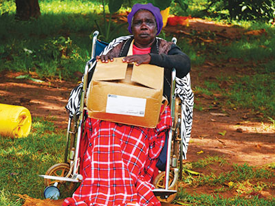 Recipient of food distribution sits in wheelchair holding box of food