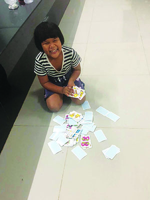 Young girl smiling and playing with cards