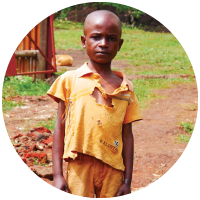 A just-rescued child standing in tattered clothing