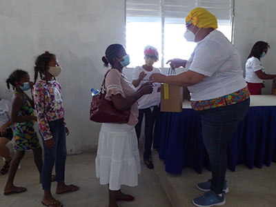 A Kinship Project member hands out hygiene supplies to community members.