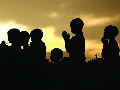 Silhouettes of children praying in front of a sunset