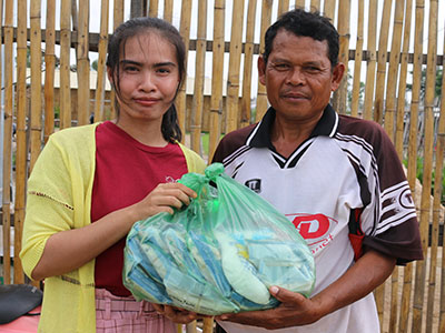 A Cambodian man receiving food from our Kinship Project