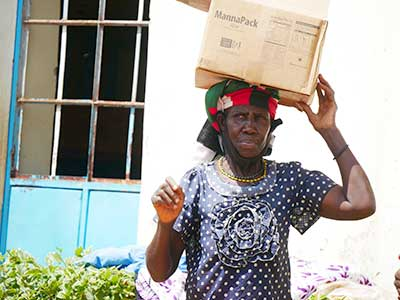 A woman in Kenya carries a box of meals on her head