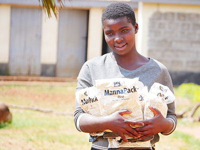 Young girl in Kenya holds packs of food in her arms